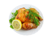 Grilled chicken with lemon and greens on plate iso Royalty Free Stock Photo