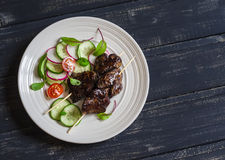 Grilled chicken liver kebabs and fresh vegetable salad Stock Photo