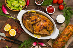 Grilled chicken marinated in balsamic sauce, spicy Italian herbs and fresh lemon. Restaurant supply on a wooden table Royalty Free Stock Image