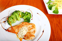 Grilled chicken meal. Closeup of a grilled chicken and broccoli meal on a white plate with sauce Stock Image