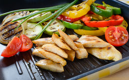 Grilled chicken meat on grill with vegetables Stock Photo