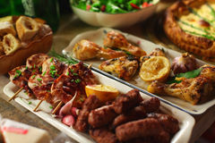 Grilled chicken meat and sausages, pie and salad for dinner Stock Images