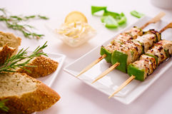 Grilled chicken and peppers on a skewer in restaurant setting. Barbeque Grilled chicken and peppers on skewer served on rectangular plate in restaurant setting Stock Photo