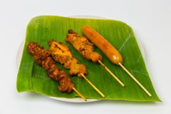 Grilled chicken and roasted sausage with wooden sticks in a whit. E plate, banana leaves on a white backdrop Royalty Free Stock Photo
