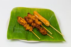 Grilled chicken and roasted sausage with wooden sticks in a whit. E plate, banana leaves on a white backdrop Stock Photo