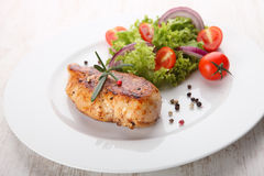 Grilled chicken salad. Grilled chicken and salad on wooden table Royalty Free Stock Photo