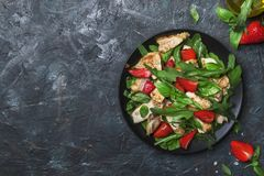 Grilled chicken salad with fresh strawberries and spicy arugula, dark kitchen table background, top view stock photo