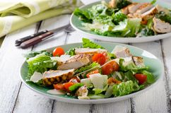 Grilled chicken salad with tomatoes and parmesan. Cheese on white wooden background Stock Photography