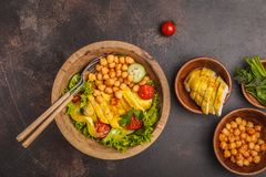 Grilled chicken salad with vegetables and chickpeas in a wooden. Bowl on a dark background, copy space, top view. Healthy balanced diet concept Royalty Free Stock Photo