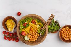 Grilled chicken salad with vegetables and chickpeas in a wooden. Bowl on a white background, copy space, top view. Healthy balanced diet concept Royalty Free Stock Photography