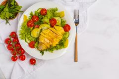 Grilled chicken salad with vegetables in a white plate on a whit. E background, copy space, top view. Healthy balanced diet concept Stock Images