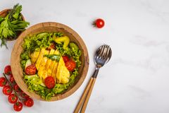Grilled chicken salad with vegetables in a wooden bowl on a whit. E background, copy space, top view. Healthy balanced diet concept Royalty Free Stock Photo