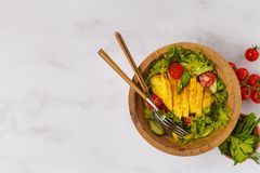 Grilled chicken salad with vegetables in a wooden bowl on a whit. E background, copy space, top view. Healthy balanced diet concept Royalty Free Stock Photography