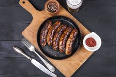 Juicy grilled chicken sausages on a dark wooden background royalty free stock image