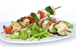 Grilled chicken skewers. Grilled chicken and vegetable skewers on a white plate stock images