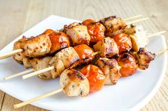 Grilled chicken skewers with cherry tomatoes. Grilled spicy chicken skewers with cherry tomatoes royalty free stock photos