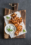 Grilled chicken skewers and tzatziki sauce on a wooden cutting board on dark background. Top view stock photos