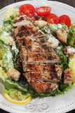 Grilled chicken steak with caesar salad Royalty Free Stock Images