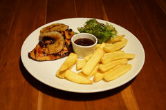 Grilled chicken steak with Golden French fries potatoes and vegetables in white plate on wooden table Royalty Free Stock Images