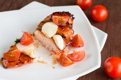 Grilled chicken steak with mozzarella and cherry tomatoes Royalty Free Stock Images