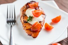 Grilled chicken steak with mozzarella and cherry tomatoes Royalty Free Stock Image