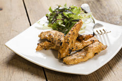 Grilled chicken strips with side salad. Delicious chicken strips with a side salad on a white square plate on a wooden table top Stock Photos