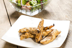 Grilled chicken strips  with spices and side salad. Barbeque chicken strips on a white plate with a side salad on a wooden table Stock Photography