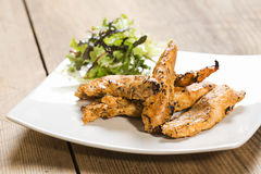 Grilled chicken strips  with spices and side salad Stock Images