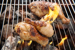 Grilled chicken thigh over flames on a barbecue Royalty Free Stock Photography