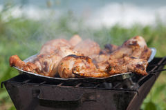Grilled chicken thighs on the flaming grill. Royalty Free Stock Images
