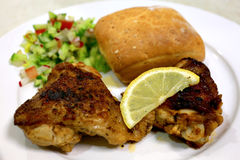 Grilled chicken thighs salad meal. A  meal of grilled chicken thighs served with a chopped salad and bread roll Stock Photos