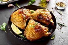 Grilled chicken thighs. Tasty grilled chicken thighs on plate over black stone table stock image