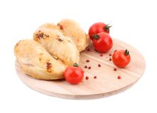 Grilled chicken with tomatoes on wood platter. Royalty Free Stock Image