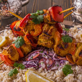 Grilled chicken and vegetable kebabs served with rice and salad. Royalty Free Stock Images