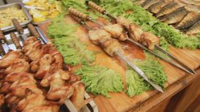 Grilled chicken and barbecue meat with salad at the market. A lot of grilled food. Shashlik. Moving camera. stock footage