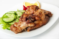 Grilled chicken on a white plate. With vegetables on the background Royalty Free Stock Images