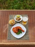 Grilled chicken on white plate with parsley, salad and beer outdoors Royalty Free Stock Photography