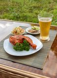 Grilled chicken on white plate with parsley, salad and beer outdoors Stock Photography