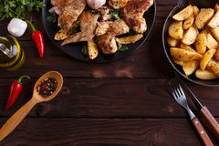 Grilled chicken wings, baked potatoes, herbs and spices on kitch royalty free stock photography