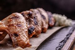 Grilled chicken wings on a black stone plate space for text royalty free stock image