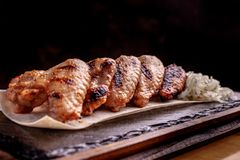 Grilled chicken wings on a black stone plate space for text royalty free stock photos