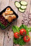 plastic container with grilled chicken wings and raw vegetables on rustic background stock photos