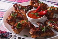 Grilled chicken wings with chili sauce on a plate close-up. hori Royalty Free Stock Photo
