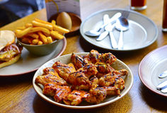 Grilled Chicken Wings & Chips on Restaurant`s Dining Table. Grilled Chicken Wings Placed on Restaurant`s Dining Table, with Chips, Knife and Plates Blurred at Royalty Free Stock Images