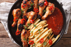 Grilled chicken wings with french fries and ketchup close-up. Ho Stock Image