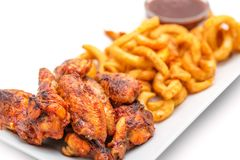 Grilled chicken wings with french fries an tomato sauce on white plate Royalty Free Stock Photos