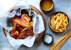 Grilled chicken wings with french fries in a wooden bowl on the aluminum background Stock Image