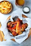 Grilled chicken wings with french fries in a wooden bowl on the aluminum background Stock Photos
