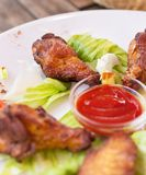 Grilled chicken wings with ketchup and greens. Royalty Free Stock Photography