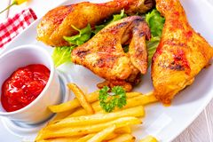 Grilled chicken wings,legs,chips and vegetables. A Grilled chicken wings,legs,chips and vegetables royalty free stock image